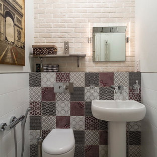 Photo of a contemporary cloakroom in Moscow with a two-piece toilet, multi-coloured tiles, white walls and a pedestal sink.