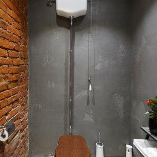 Idée de décoration pour un WC et toilettes urbain de taille moyenne avec un WC séparé, un carrelage gris, des carreaux de béton, un mur rouge, béton au sol, un lavabo de ferme et un sol gris.
