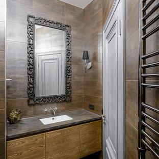 На фото: с высоким бюджетом туалеты среднего размера в классическом стиле с плоскими фасадами, коричневой плиткой, керамогранитной плиткой, полом из керамогранита, врезной раковиной, столешницей из искусственного камня, фасадами цвета дерева среднего тона и коричневым полом