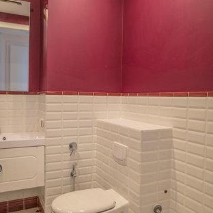 Aménagement d'un grand WC et toilettes contemporain avec des portes de placard blanches, un WC suspendu, un carrelage blanc, un carrelage métro, un mur rose et un lavabo intégré.