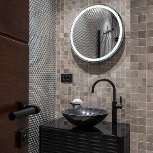 Свежая идея для дизайна: туалет в стиле лофт с черными фасадами, бежевой плиткой, серой плиткой, настольной раковиной, бежевым полом и черной столешницей - отличное фото интерьера