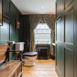Photo of a medium sized victorian cloakroom in London with a two-piece toilet, green walls, light hardwood flooring and beige floors.