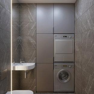 Idee per un piccolo bagno di servizio design con WC sospeso, piastrelle grigie, piastrelle in gres porcellanato, pavimento in gres porcellanato, lavabo sospeso, pavimento grigio, ante lisce, ante grigie e pareti grigie