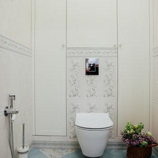 他の地域の小さいトランジショナルスタイルのおしゃれなトイレ・洗面所 (落し込みパネル扉のキャビネット、淡色木目調キャビネット、壁掛け式トイレ、ベージュのタイル、セラミックタイル、ベージュの壁、磁器タイルの床、壁付け型シンク、ターコイズの床) の写真