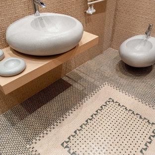 На фото: туалеты в средиземноморском стиле с инсталляцией, бежевой плиткой, настольной раковиной и разноцветным полом