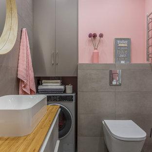 Imagen de aseo contemporáneo con armarios con paneles lisos, paredes rosas, lavabo sobreencimera y suelo gris