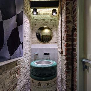 Пример оригинального дизайна: туалет в стиле лофт с разноцветными стенами, полом из галечной плитки, накладной раковиной и разноцветным полом