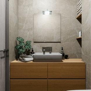 Идея дизайна: маленький туалет в скандинавском стиле с плоскими фасадами, коричневыми фасадами, инсталляцией, коричневой плиткой, керамической плиткой, коричневыми стенами, полом из керамической плитки, накладной раковиной, столешницей из дерева, черным полом и коричневой столешницей