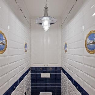 Cette photo montre un petit WC et toilettes bord de mer avec un WC suspendu, un carrelage bleu, un carrelage blanc, des carreaux de céramique, un sol en carrelage de céramique et un sol blanc.