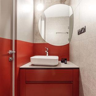 На фото: туалет в современном стиле с плоскими фасадами, оранжевыми фасадами, полом из терраццо, настольной раковиной, серым полом и белой столешницей с