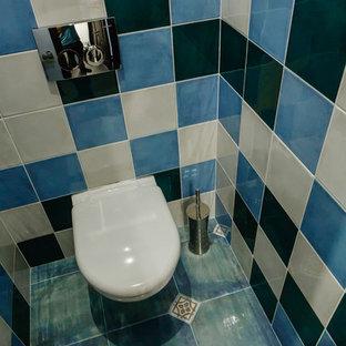 他の地域の小さいコンテンポラリースタイルのおしゃれなトイレ・洗面所 (フラットパネル扉のキャビネット、白いキャビネット、壁掛け式トイレ、青いタイル、セラミックタイル、青い壁、磁器タイルの床、ターコイズの床) の写真