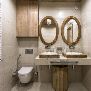 Неиссякаемый источник вдохновения для домашнего уюта: туалет среднего размера в современном стиле с настенным унитазом, бежевой плиткой, полом из керамической плитки, настольной раковиной и бежевым полом