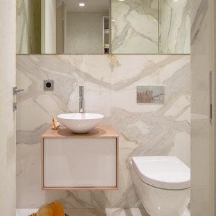 Неиссякаемый источник вдохновения для домашнего уюта: туалет в современном стиле с плоскими фасадами, белыми фасадами, инсталляцией, белыми стенами, мраморным полом, настольной раковиной, белым полом, мраморной плиткой и бежевой столешницей
