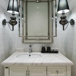 Идея дизайна: туалет в классическом стиле с белыми фасадами, белой плиткой, керамической плиткой, врезной раковиной, столешницей из гранита и фасадами с утопленной филенкой
