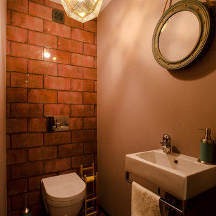 Inspiration for a small urban cloakroom in Other with a wall mounted toilet, red tiles, ceramic tiles, pink walls, porcelain flooring and a wall-mounted sink.
