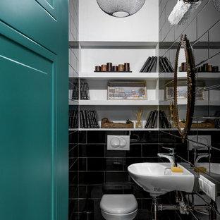 На фото: туалет в современном стиле с инсталляцией, черной плиткой, белыми стенами, подвесной раковиной и белым полом