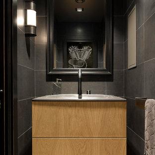 Идея дизайна: туалет в современном стиле с плоскими фасадами, светлыми деревянными фасадами, серой плиткой и монолитной раковиной