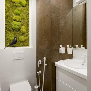 Пример оригинального дизайна: маленький туалет в современном стиле с плоскими фасадами, белыми фасадами, инсталляцией, белой плиткой, коричневой плиткой, накладной раковиной и коричневым полом