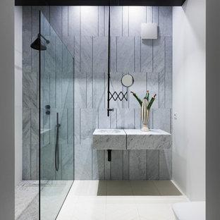 Immagine di un bagno di servizio design di medie dimensioni con ante di vetro, ante grigie, bidè, piastrelle grigie, piastrelle di marmo, pareti grigie, parquet chiaro, lavabo sottopiano, top in marmo, pavimento bianco e top grigio