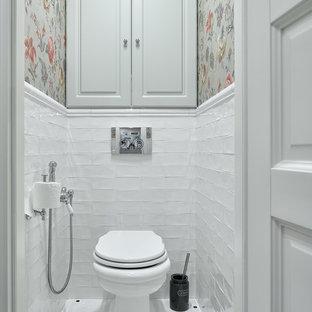 Idee per un bagno di servizio chic con ante con bugna sagomata, ante grigie, piastrelle bianche, pareti multicolore, pavimento con piastrelle a mosaico, pavimento bianco e WC a due pezzi