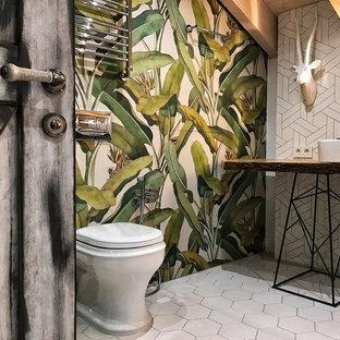 Idee per un bagno di servizio industriale di medie dimensioni con WC sospeso, piastrelle bianche, piastrelle di vetro, pareti grigie, pavimento con piastrelle in ceramica, lavabo da incasso, top in legno, pavimento bianco e top beige