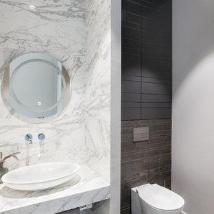 На фото: маленький туалет в современном стиле с инсталляцией, белой плиткой, мраморной плиткой, белыми стенами, настольной раковиной, мраморной столешницей, серым полом и белой столешницей с