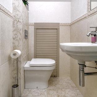 Пример оригинального дизайна интерьера: туалет в стиле современная классика с раздельным унитазом, бежевой плиткой, подвесной раковиной и бежевым полом