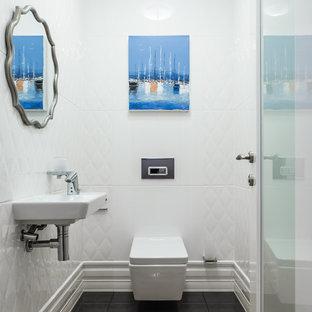 Пример оригинального дизайна: туалет в стиле современная классика с инсталляцией, белой плиткой, подвесной раковиной и черным полом
