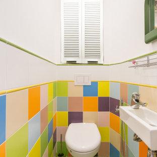 Cette image montre un petit WC et toilettes design avec un WC suspendu, un carrelage multicolore, des carreaux de céramique, un sol en carrelage de céramique, un lavabo suspendu, un sol vert et un mur blanc.