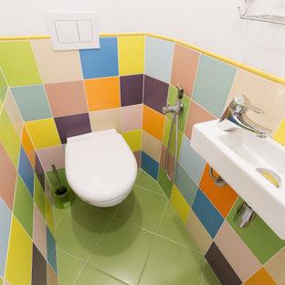 Kleine Gästetoilette mit Wandtoilette, farbigen Fliesen, Keramikfliesen, bunten Wänden, Keramikboden, Wandwaschbecken und grünem Boden in Sonstige