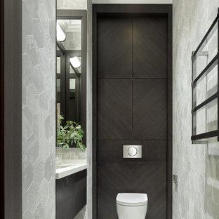 На фото: туалет в современном стиле с плоскими фасадами, инсталляцией, врезной раковиной, серым полом, белой столешницей и подвесной тумбой