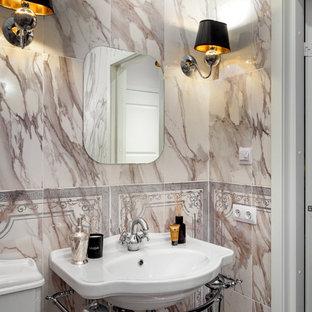 На фото: туалет в стиле современная классика с бежевой плиткой, консольной раковиной, раздельным унитазом, мраморной плиткой и разноцветными стенами с