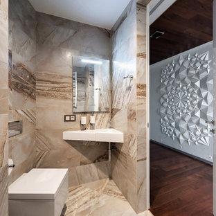 Cette image montre un très grand WC et toilettes design avec un WC suspendu, un carrelage beige, un mur beige, un lavabo suspendu, un sol beige, un placard à porte plane et un sol en carrelage de porcelaine.