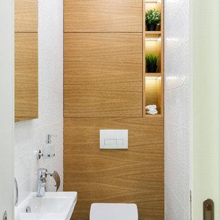 На фото: туалет в современном стиле с плоскими фасадами, фасадами цвета дерева среднего тона, инсталляцией, белой плиткой, керамической плиткой, полом из керамической плитки, подвесной раковиной и бирюзовым полом с