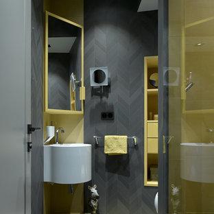 На фото: туалеты в современном стиле с черной плиткой, подвесной раковиной, черными стенами и черным полом