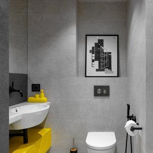 Modelo de aseo actual con armarios con paneles lisos, puertas de armario amarillas, sanitario de pared, baldosas y/o azulejos grises, lavabo integrado, suelo gris y encimeras blancas