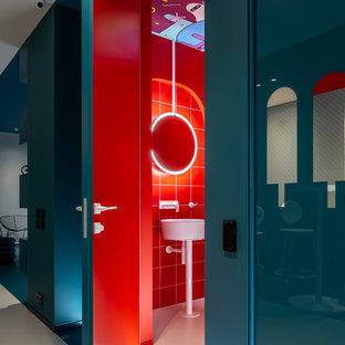 Aménagement d'un petit WC et toilettes contemporain avec un placard à porte plane, des portes de placard rouges, un WC suspendu, un carrelage rouge, des carreaux de céramique, un mur rouge, un lavabo suspendu et un sol blanc.