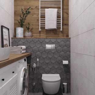 На фото: с невысоким бюджетом маленькие туалеты в скандинавском стиле с фасадами с филенкой типа жалюзи, белыми фасадами, инсталляцией, серой плиткой, керамической плиткой, серыми стенами, полом из керамической плитки, настольной раковиной, столешницей из дерева, серым полом и коричневой столешницей