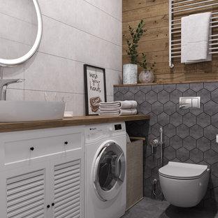 Idée de décoration pour un petit WC et toilettes nordique avec un placard à porte persienne, des portes de placard blanches, un WC suspendu, un carrelage gris, des carreaux de céramique, un mur gris, un sol en carrelage de céramique, une vasque, un plan de toilette en bois, un sol gris et un plan de toilette marron.
