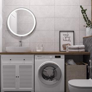 Idéer för att renovera ett litet minimalistiskt brun brunt toalett, med luckor med lamellpanel, vita skåp, en vägghängd toalettstol, grå kakel, keramikplattor, grå väggar, klinkergolv i keramik, ett fristående handfat, träbänkskiva och grått golv