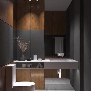 Réalisation d'un WC et toilettes design de taille moyenne avec un placard à porte shaker, des portes de placard beiges, un plan de toilette en surface solide, un sol beige, un WC séparé, un carrelage marron, des carreaux en allumettes, un mur noir, un sol en carrelage de porcelaine et un plan vasque.