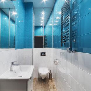 Esempio di un bagno di servizio minimal di medie dimensioni con WC sospeso, piastrelle blu, piastrelle bianche, ante di vetro, ante bianche, piastrelle in pietra, pareti bianche, pavimento in gres porcellanato, lavabo sospeso e pavimento marrone