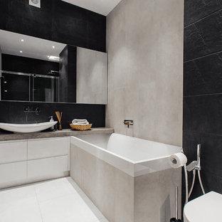 Immagine di un piccolo bagno di servizio bohémian con pareti grigie, pavimento con piastrelle in ceramica, ante lisce, ante bianche, WC sospeso, piastrelle nere, piastrelle in ceramica, lavabo da incasso e top in cemento