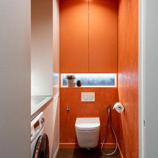 Свежая идея для дизайна: маленький туалет в стиле модернизм с плоскими фасадами, оранжевыми фасадами, инсталляцией, оранжевыми стенами, полом из винила, врезной раковиной, столешницей из искусственного камня, бежевым полом, серой столешницей и встроенной тумбой - отличное фото интерьера