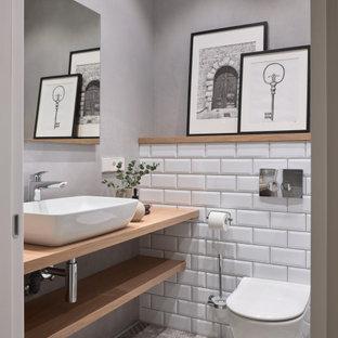 モスクワのコンテンポラリースタイルのおしゃれなトイレ・洗面所 (オープンシェルフ、壁掛け式トイレ、白いタイル、サブウェイタイル、グレーの壁、ベッセル式洗面器、ベージュの床、ブラウンの洗面カウンター) の写真