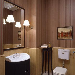 Пример оригинального дизайна интерьера: туалет в стиле современная классика с раздельным унитазом, коричневыми стенами, черными фасадами, консольной раковиной и бежевым полом
