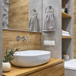 Cette image montre un petit WC et toilettes design avec un placard à porte plane, des portes de placard en bois clair, un carrelage beige, un carrelage imitation parquet, un mur gris, une vasque, un plan de toilette en bois, un plan de toilette beige et meuble-lavabo suspendu.