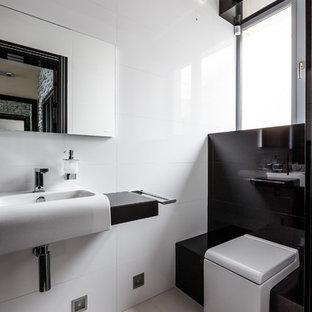 Идея дизайна: туалет в современном стиле с раздельным унитазом, белой плиткой, черной плиткой, монолитной раковиной и белым полом