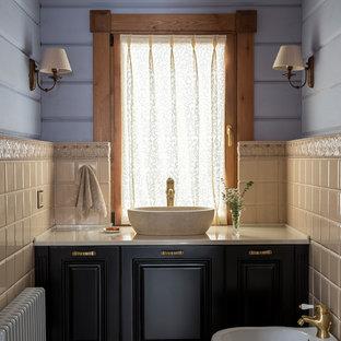 Idée de décoration pour un WC et toilettes champêtre avec un carrelage beige, des carreaux de céramique, un mur bleu, un sol en carreaux de ciment, une vasque, un plan de toilette en marbre, un plan de toilette beige, un placard avec porte à panneau surélevé, des portes de placard noires, un bidet et un sol gris.
