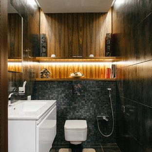 Стильный дизайн: туалет в современном стиле с плоскими фасадами, белыми фасадами, инсталляцией, черной плиткой, монолитной раковиной и серым полом - последний тренд